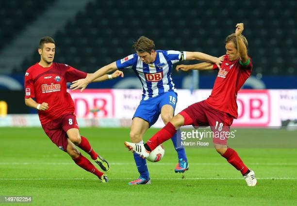 Peter Niemeyer of Berlin and Mario Vrancic and Markus Kroesche of Paberborn battle for the ball during the Second Bundesliga match between Hertha BSC...