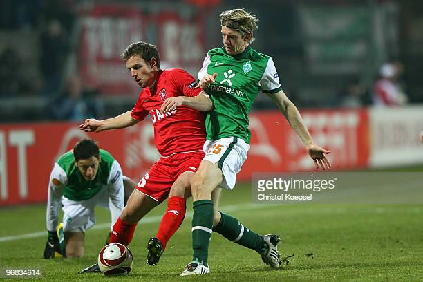 Peter Niemeyer of Bremen tackles Wout Brama of Enschede during the UEFA Europa League knockout round first leg match between FC Twente Enschede and...