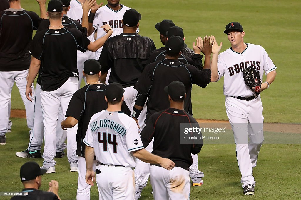 Peter O'Brien (R)#14 of the Arizona Diamondbacks high fives teammates after defeating the Colorado Rockies 11-4 in the MLB game at Chase Field on September 13, 2016 in Phoenix, Arizona.