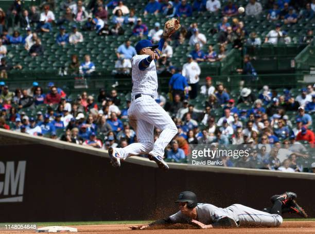 Peter O'Brien of the Miami Marlins steals second base as Javier Baez of the Chicago Cubs takes a high throw during the fourth inning at Wrigley Field...