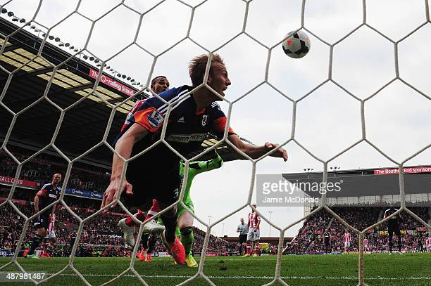 Peter Odemwingie of Stoke City scores despite the efforts of Dan Burn of Fulham on the goal line during the Barclays Premier League match between...