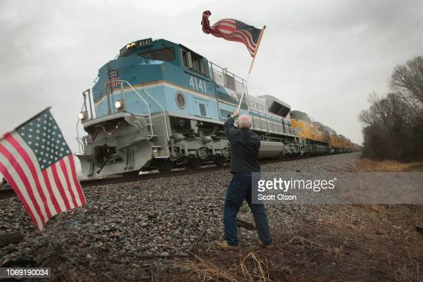 Peter Olyniec waves a flag as a train passes carrying the body of former President George HW Bush to his final resting place on December 6 2018 near...