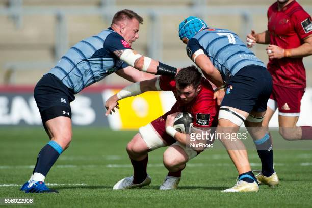 Peter O'Mahony of Munster tackled by Matthew Rees and Olly Robinson of Cardiff during the Guinness PRO14 Conference A Round 5 match between Munster...