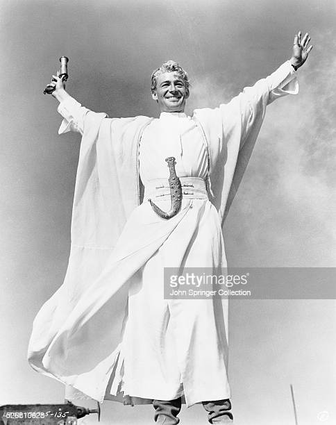 """Peter O'Toole in a scene from """"Lawrence of Arabia."""" He stands, arms outstretched, holding weapon. He smiles wickedly."""