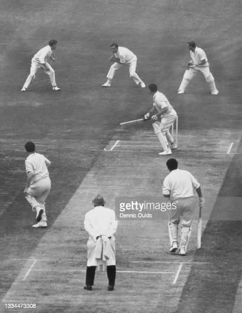 Peter Parfitt and wicketkeeper Jim Parks look on as Colin Cowdrey of England takes the catch in the slips to dismiss Neil Hawke of Australia for 13...