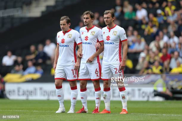 Peter Pawlett Ed Upson and Alex Gilbey of Milton Keynes Dons line up to defend a free kick during the Sky Bet League One match between Milton Keynes...