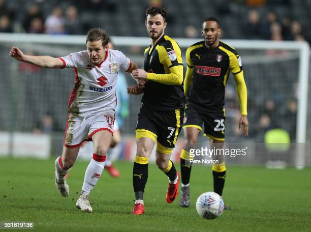 Peter Pawlett of Milton Keynes Dons looks to the ball with Anthony Forde of Rotherham United during the Sky Bet League One match between Milton...
