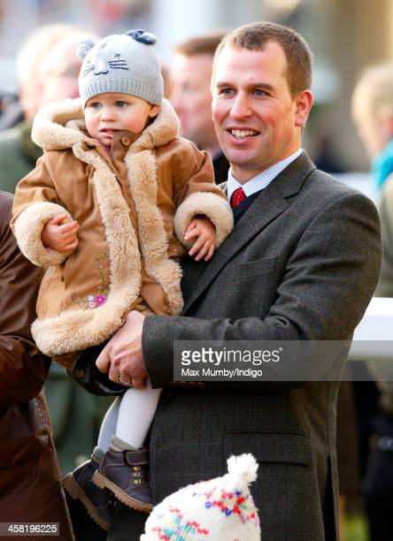 Peter Phillips carries daughter Isla Phillips as they attend the Christmas Meeting at Ascot Racecourse on December 20 2013 in Ascot England