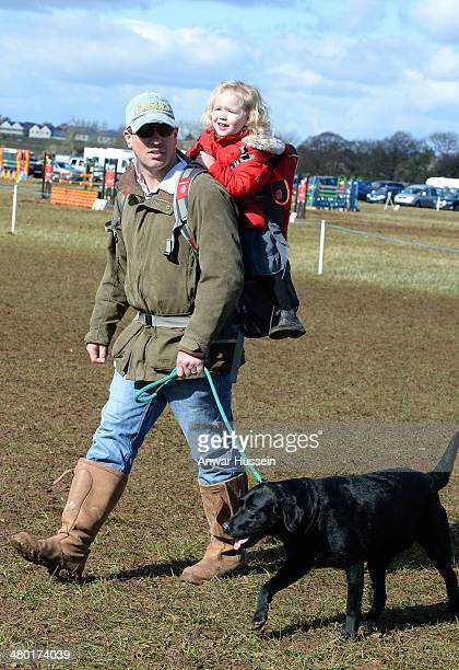 Peter Phillips carries his daughter Savannah during the Gatcombe Horse Trials at Gatcombe Park on March 23 2014 in Minchinhampton England