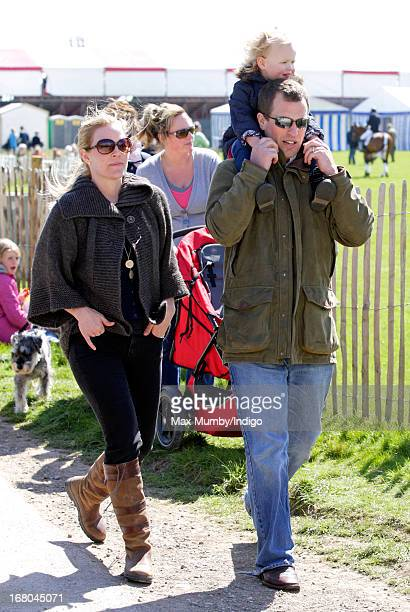Peter Phillips carries his daughter Savannah Phillips on his shoulders as they and his wife Autumn Phillips attend day 3 of the Badminton Horse...