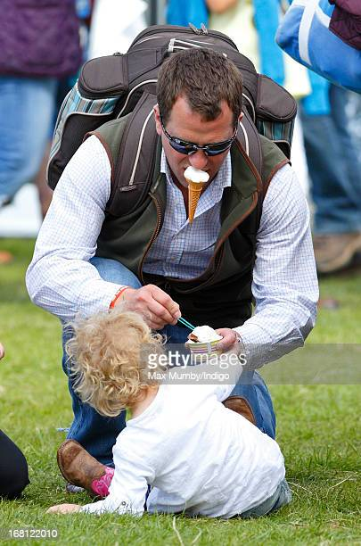 Peter Phillips holds an ice cream in his mouth whilst giving his daughter Savannah Phillips an ice cream as they attend day 4 of the Badminton Horse...