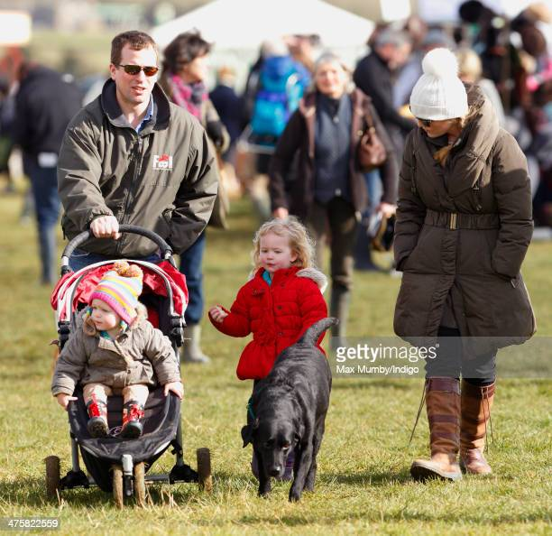 Peter Phillips pushes daughter Isla Phillips in her pushchair whilst eldest daughter Savannah Phillips walks the family dog along with Autumn...