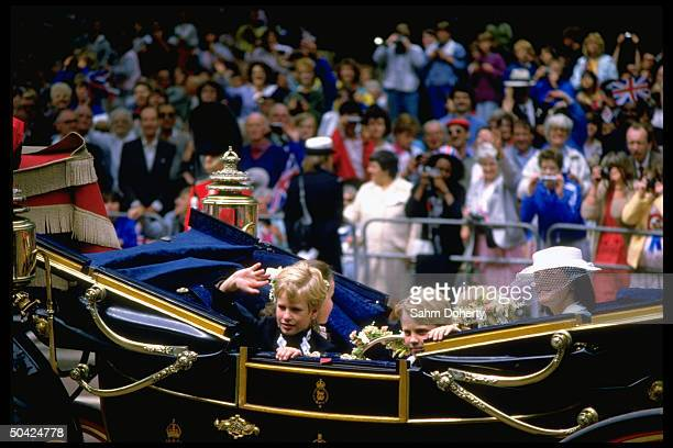 Peter Phillips riding with unidentified children in royal carriage along fanlined route to church wedding of England's Prince Andrew to Sarah Ferguson
