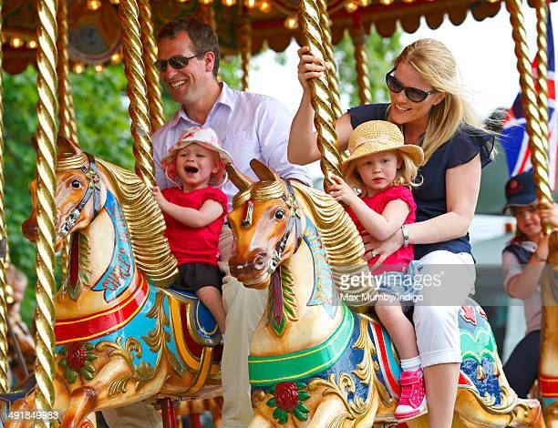 Peter Phillips with daughter Isla Phillips and Autumn Phillips with daughter Savannah Phillips ride a merry go round during day 4 of the Royal...