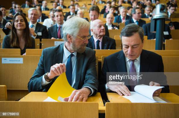 Peter Praet chief economist at the European Central Bank left speaks with Mario Draghi president of the European Central Bank as they sit in the...