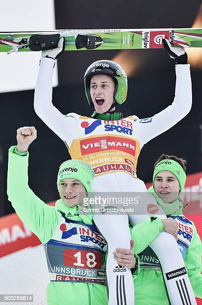 Peter Prevc of Slovenia celebrates with team mates Anze Lanisek and Tilen Bartol as he wins the Innsbruck 64th Four Hills Tournament ski jumping...