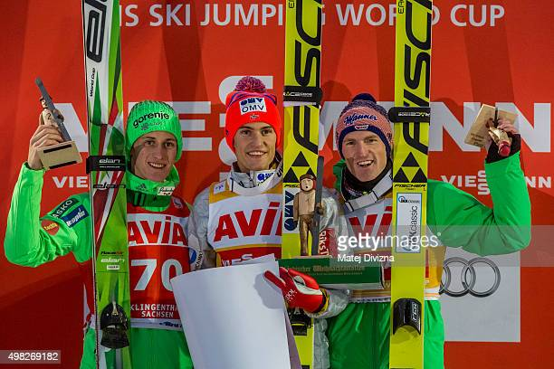 Peter Prevc of Slovenia winner DanielAndre Tande of Norway and Severin Freund of Germany pose for photographers after the individual competition at...