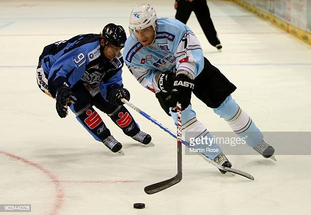 Peter Ratchuk of Hamburg and Rene Roethke of Straubing fight for the puck during the DEL match between Hamburg Freezers and Straubing Tigers at the...