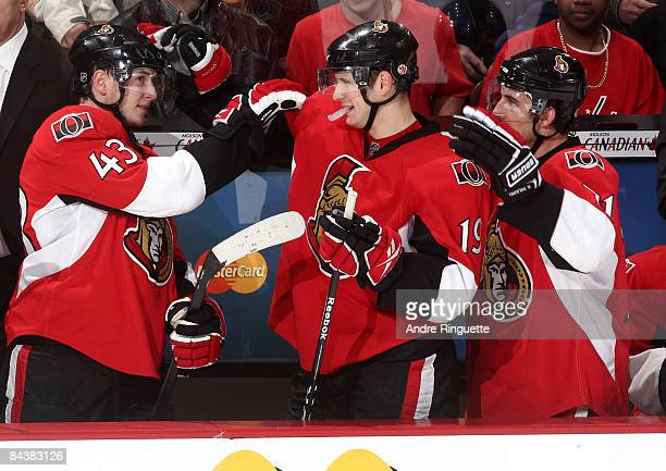 Peter Regin, Jason Spezza and Nick Foligno of the Ottawa Senators celebrate their win against the Washington Capitals from the players' bench at...