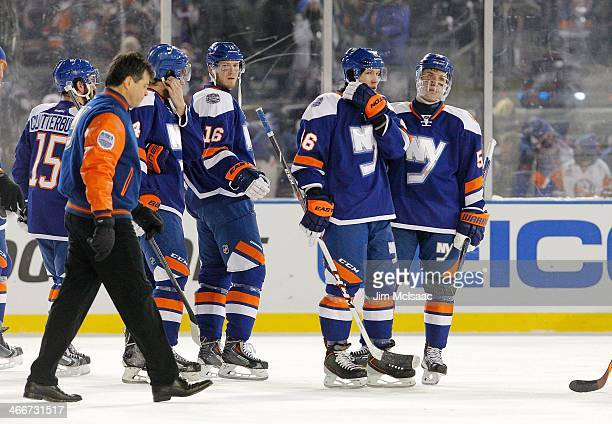 Peter Regin, Matt Donovan and Casey Cizikas of the New York Islanders look on after the 2014 Coors Light NHL Stadium Series game against the New York...