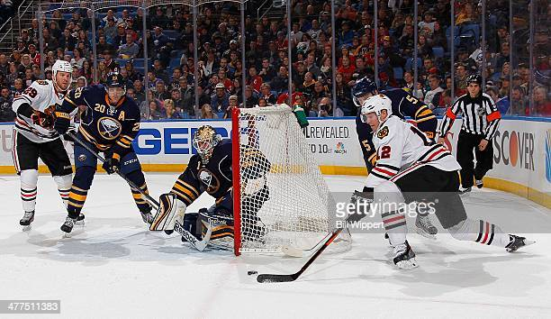 Peter Regin of the Chicago Blackhawks carries the puck from behind the net defended by Chad Ruhwedel, Jhonas Enroth and Henrik Tallinder of the...