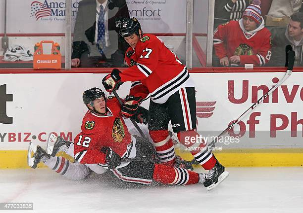 Peter Regin of the Chicago Blackhawks collides with teammate Sheldon Brookbank and Matt Calvert of the Columbus Blue Jackets as they battle for the...