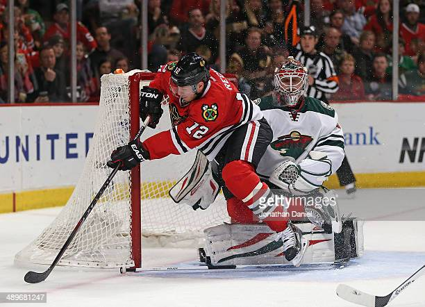 Peter Regin of the Chicago Blackhawks crahses into the net next to Ilya Bryzgalov of the Minnesota Wild in Game Five of the Second Round of the 2014...