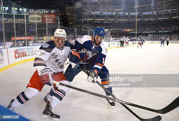 Peter Regin of the New York Islanders and John Moore of the New York Rangers vie for position along the end boards in the first period during the...