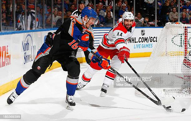 Peter Regin of the New York Islanders battles for the puck with Jay Harrison of the Carolina Hurricanes during the second period at Nassau Veterans...