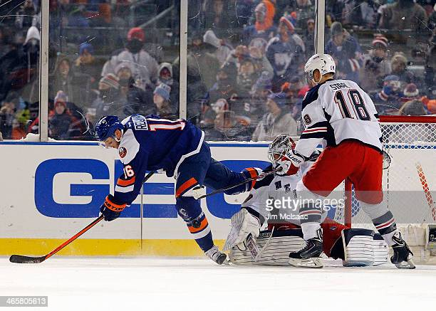 Peter Regin of the New York Islanders is tripped up as Henrik Lundqvist and Marc Staal of the New York Rangers keep their eyes on the puck during the...