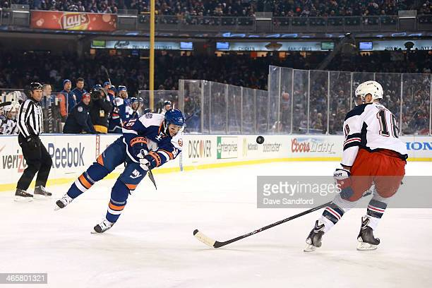 Peter Regin of the New York Islanders shoots the puck past Marc Staal of the New York Rangers in the first period during the 2014 Coors Light NHL...