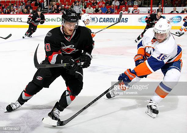 Peter Regin of the New York Islanders sweep checks Riley Nash of the Carolina Hurricanes during their NHL game at PNC Arena on November 7, 2013 in...