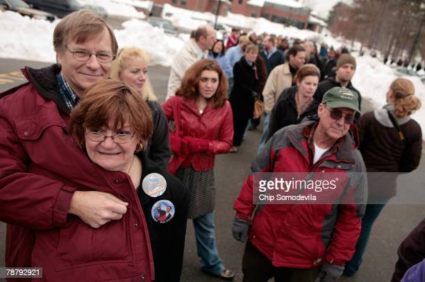 Peter Reilley helps keep his wife Jayne GalleyReilley warm while waiting in line for a rally for at Democratic presidential hopeful Sen Barack Obama...