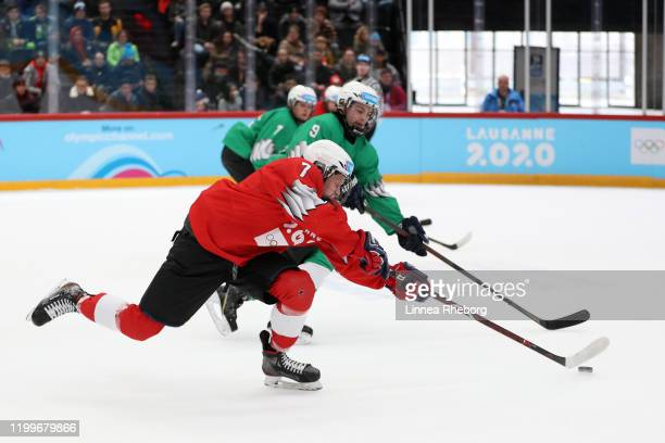 Peter Repcik of Slovakia and Team Red controls the puck as he is challenged by Alessandro Segafredo of Italy and Team Green during their Men's Mixed...