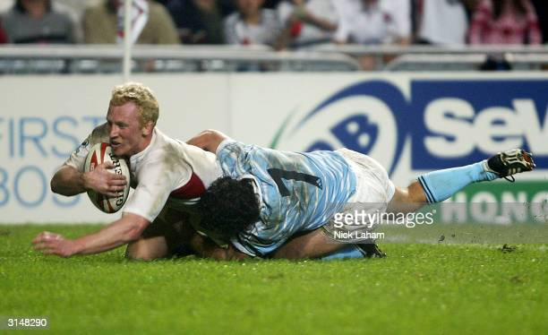 Peter Richards of England scores despite the tackle from Lucio Lopez Fleming of Argentina in the Cup Final during the Hong Kong World Sevens day...