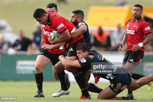 Peter Samu of the Crusaders tries to break the tackle of Lima Sopoaga and Dillon Hunt of the Highlanders during the Super Rugby trial match between...