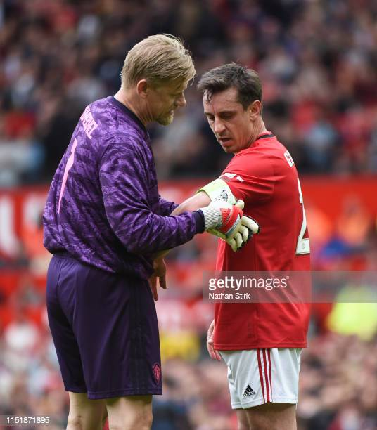 Peter Schmeichel of Manchester United gives the captain's armband to Gary Neville during the Manchester United '99 Legends and FC Bayern Legends at...