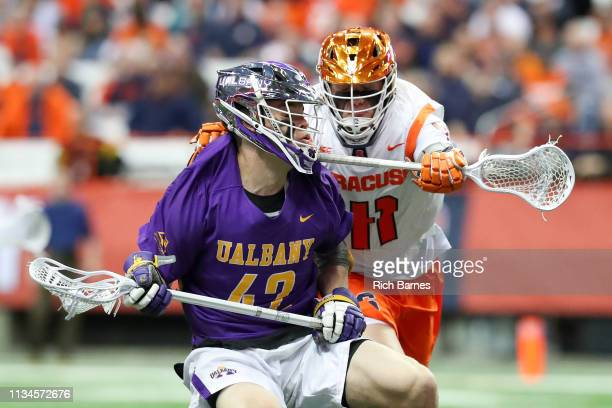 Peter Schwab of the Albany Great Danes gets checks in the back by Brett Barlow of the Syracuse Orange during the second half at the Carrier Dome on...