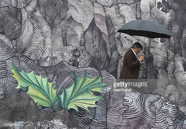 Peter Schwenkow CEO and Chairman of DEAG walks with an umbrella under rain on the set for the Seefestspiele 2011 music festival ahead of the...
