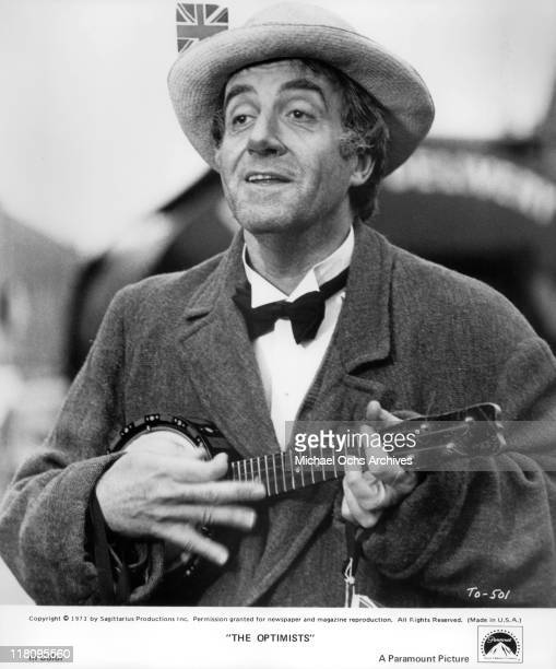 Peter Sellers plays ukulele in a scene from the film 'The Optimists' 1973