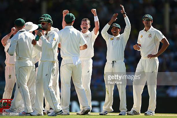 Peter Siddle and Usman Khawaja of Australia celebrate after seeing the replay displayed on the screen to dismiss JeanPaul Duminy of South Africa...