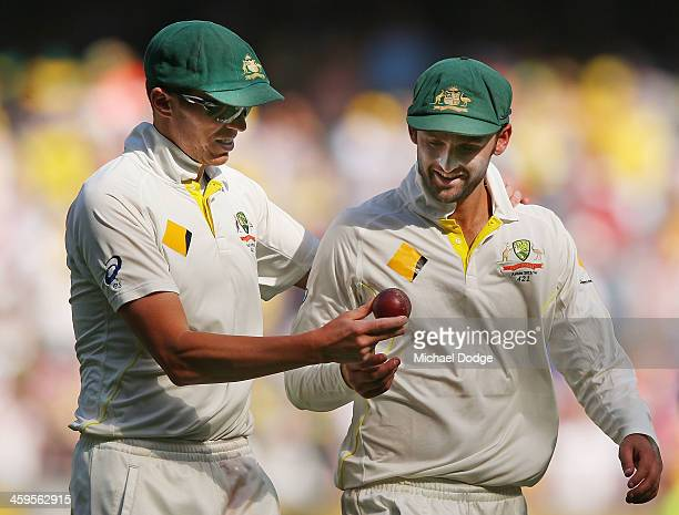 Peter Siddle hands Nathan Lyon of Australia the ball after he got 5 wickets in an inniings during day three of the Fourth Ashes Test Match between...
