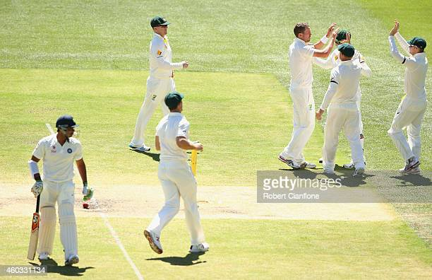 Peter Siddle of Australia celebrates after taking the wicket of Karn Sharma of India during day four of the First Test match between Australia and...