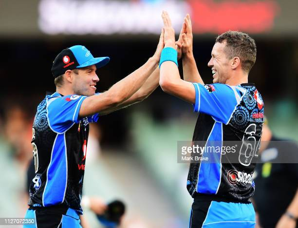 Peter Siddle of the Adelaide Strikers celebrates after taking the wicket of Ben Cutting of the Heat with Ben Laughlin of the Adelaide Strikers during...