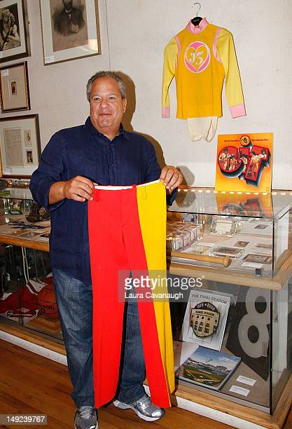 Peter Siegel holds Michael Jackson's pants while Jackson's shirt and album cover hang behind him at a press preview for the Gotta Have Rock and Roll...