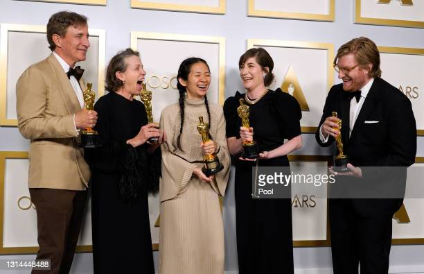 """Peter Spears, Frances McDormand, Chloe Zhao, Mollye Asher, and Dan Janvey, winners of Best Picture for """"Nomadland,"""" pose in the press room at the..."""