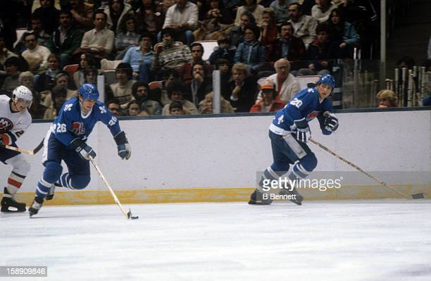 Peter Stastny of the Quebec Nordiques skates with the puck along side of his brother/teammate Anton Stastny during an NHL game against the New York...