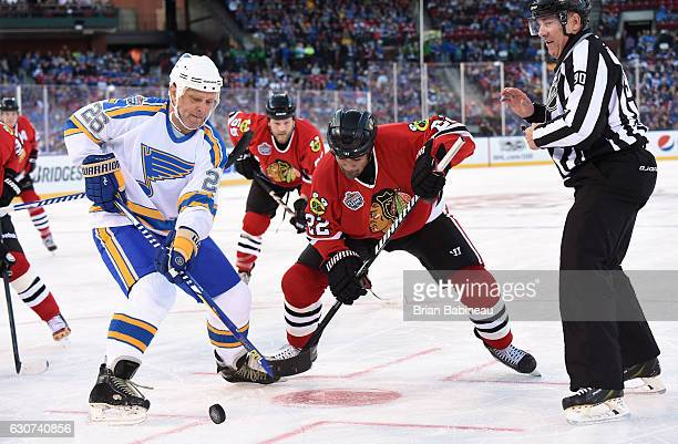 Peter Stastny of the St Louis Blues and Jamal Mayers of the Chicago Blackhawks take a faceoff during the 2017 Bridgestone NHL Winter Classic Alumni...