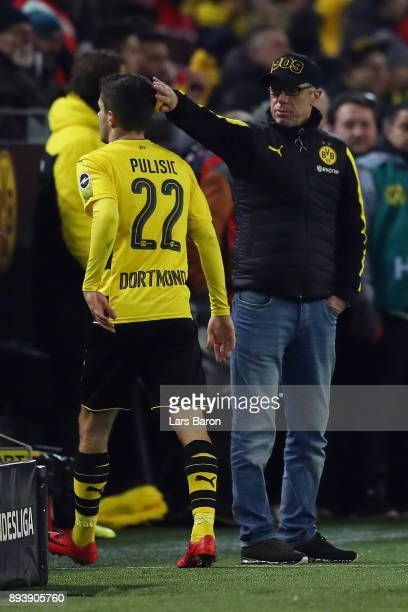 Peter Stoeger coach of Dortmund congratulates Christian Pulisic of Dortmund as he is substituted during the Bundesliga match between Borussia...