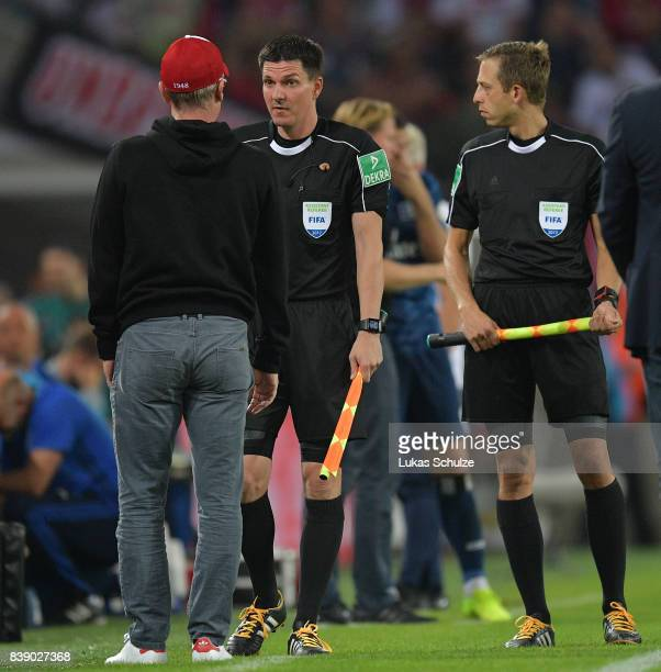 Peter Stoeger coach of Koeln speak with linesman mark Borsch and Stefan Lupp while the match is halted during the Bundesliga match between 1 FC Koeln...